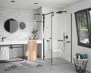 Das Bild zeigt ein sehr helles, offenes Bad mit streng geometrischen Linien, die über die Profile der Dusche, des Waschtischs und der Accessoires gezogen werden.