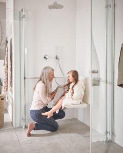 Das Bild zeigt eine lächelnde Frau mit grauem, langem Haar und ein kleines Kind, das auf einem Klappsitz in einer Dusche sitzt.